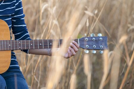 Guitar in the grass. Close up of a hand with a guitar in a brown meadow background. Banque d'images - 138734962