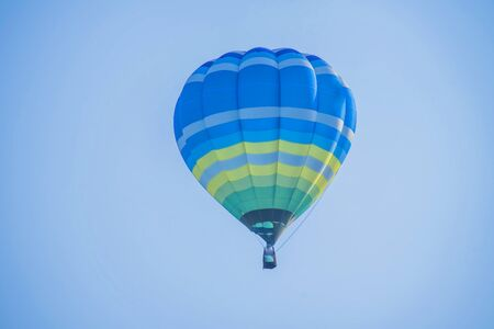 Colorful  balloon above a flower field at a national balloon festival, Natural elements and a blue sky background.