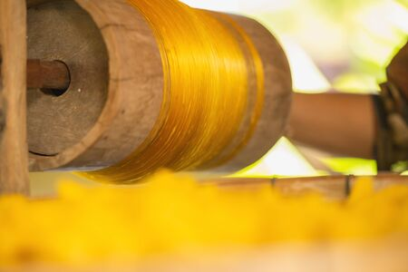 Wheel Spinning Yarn with Yellow Thread to work for Weaving machine and Thai traditional Silk. Artists artisans handicrafts handmade manufacturing motton silk hand loom Thai.  Banque d'images