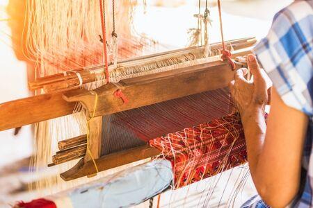 Wheel Spinning Yarn with Yellow Thread to work for Weaving machine and Thai traditional Silk. Artists artisans handicrafts handmade manufacturing motton silk hand loom Thai.  Zdjęcie Seryjne