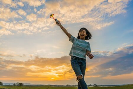 Happy girl running with a kite at sunset outdoors, Little girl running with kite in the field on summer day with sunset.