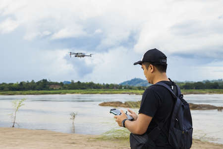 Man operating a drone with remote control. Drone with high resolution digital camera on the river and sky.