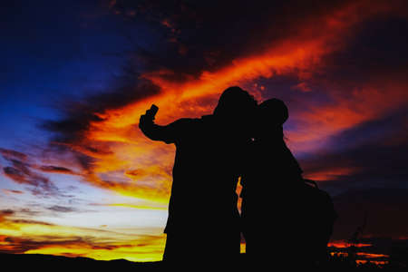 Silhouettes couples with sunset , Romantic couple in love together with sunset, Silhouettes of young man and woman in love on holidays or honeymoon.