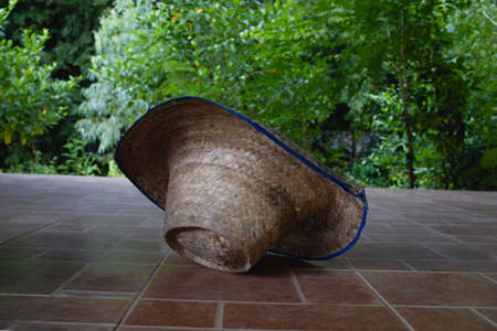 Asian country farmer's traditional straw hat is placed on the ground.