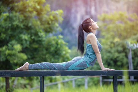 Portrait of gorgeous young woman practicing yoga with nature background. Woman Yoga - relax in nature. Calmness and relax, happiness.