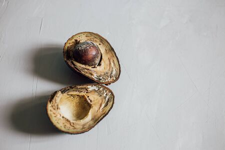 Halves of rotten spoiled avocado fruit and seeds on a gray background. Close-up. Copy space. Stop wasting food concepts, food poisoning, eating stale food. Throw out stale products. Eye level shooting.