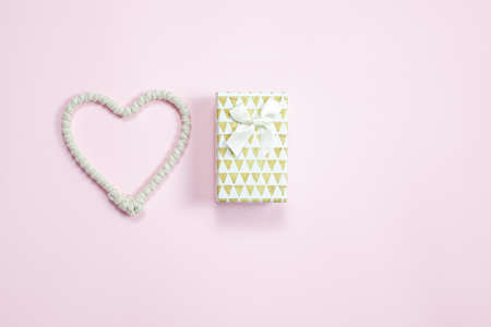 Heart made of rope and a gift on a pink background. Valentine's Day background. Valentine's Day concept. Flat lounger, top view, copy space. Reklamní fotografie