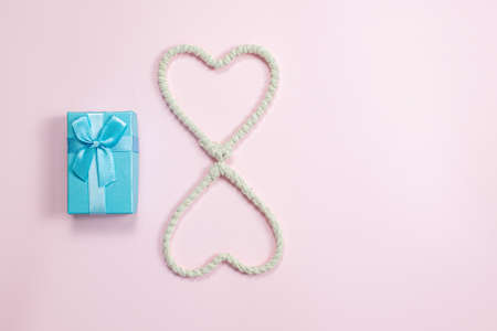 Heart made of rope and a gift on a pink background. Valentine's Day background. Valentine's Day concept. Flat lounger, top view, copy space.