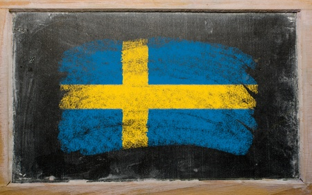 Chalky Swedish flag painted with color chalk on old blackboard photo