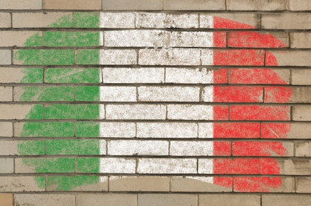 Chalky italian flag painted with color chalk on grunge old brick wall photo