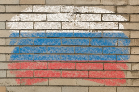 Chalky russian flag painted with color chalk on grunge old brick wall photo