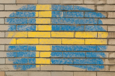 Chalky swedish flag painted with color chalk on grunge old brick wall photo
