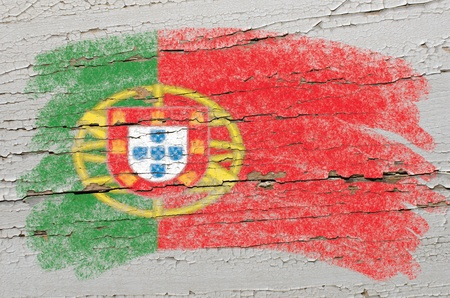 Chalky portugese flag painted with color chalk on grunge wooden texture photo