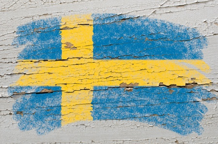 education in sweden: Chalky swedish flag painted with color chalk on grunge wooden texture