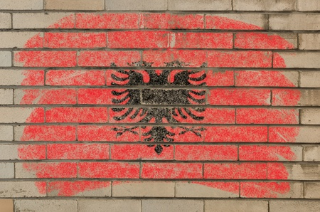 Chalky albanian flag painted with color chalk on grunge old brick wall photo