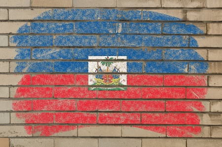 Chalky haitian flag painted with color chalk on grunge old brick wall photo