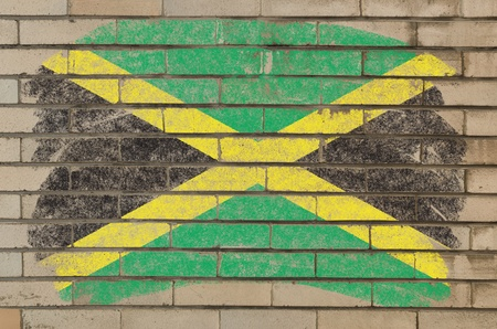 Chalky jamaican flag painted with color chalk on grunge old brick wall photo