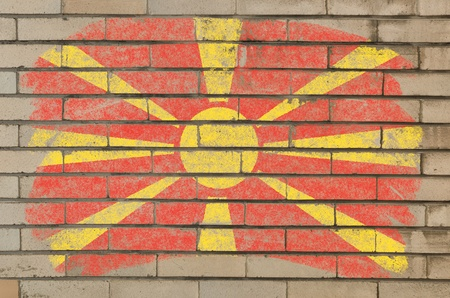 Chalky macedonian flag painted with color chalk on grunge old brick wall photo