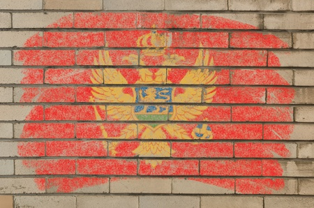 Chalky montenegrian flag painted with color chalk on grunge old brick wall photo