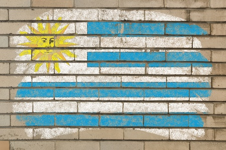 Chalky uruguay flag painted with color chalk on grunge old brick wall photo