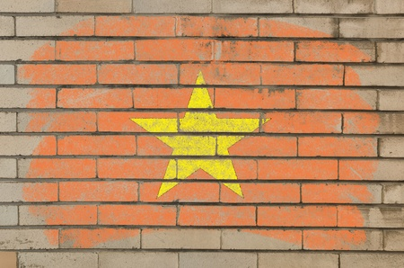 Chalky vietnamese flag painted with color chalk on grunge old brick wall photo