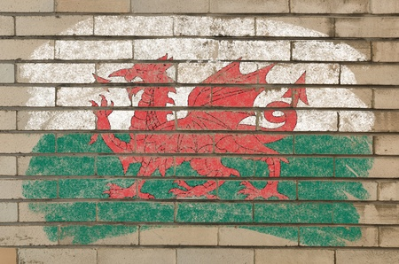 Chalky welsh flag painted with color chalk on grunge old brick wall photo
