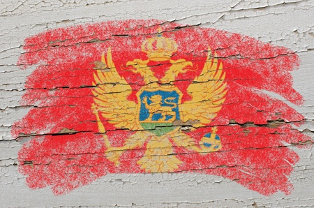 Chalky  montenegrian flag painted with color chalk on grunge wooden texture photo