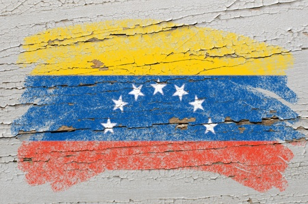 Chalky venezuelan flag painted with color chalk on grunge wooden texture photo