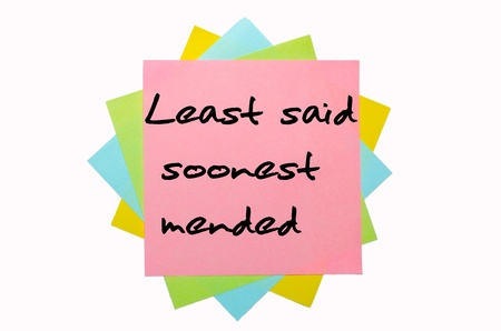 text Least said soonest mended written by hand font on bunch of colored sticky notes