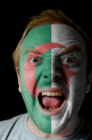 algerian flag: Low key portrait of an angry man whose face is painted in colors of algerian flag