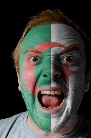 Algierski: Niski klucz portret gniewnego człowieka, którego twarz jest pomalowana w kolorach flagi Algierii Zdjęcie Seryjne