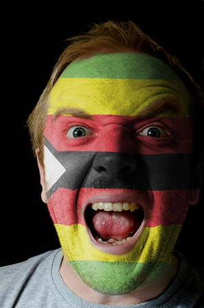 Low key portrait of an angry man whose face is painted in colors of zimbabwe flag Stock Photo - 11001964