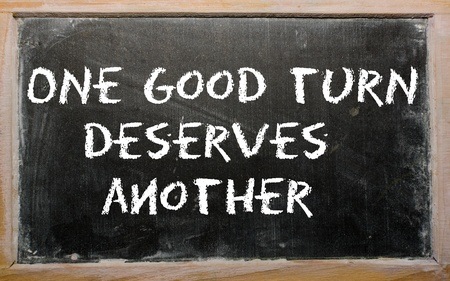 Blackboard writings &quot,One good turn deserves another&quot, Stock Photo - 11001992