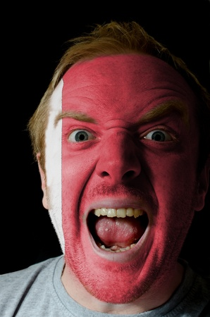 whose: Low key portrait of an angry man whose face is painted in colors of bahrain flag Stock Photo