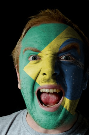 Low key portrait of an angry man whose face is painted in colors of brazilian flag photo
