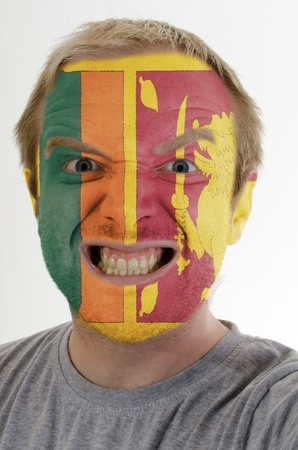whose: High key portrait of an angry man whose face is painted in colors of srilanka flag