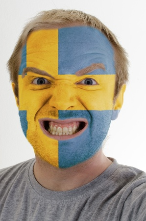 High key portrait of an angry man whose face is painted in colors of swedish flag photo