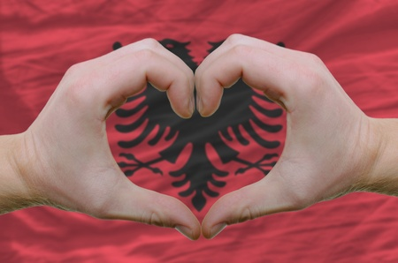 Gesture made by hands showing symbol of heart and love over Albanian flag photo