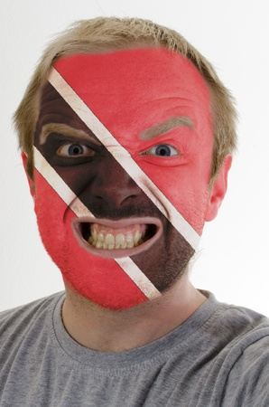 whose: High key portrait of an angry man whose face is painted in colors of trinidad and tobago flag Stock Photo