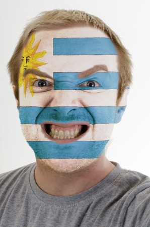 High key portrait of an angry man whose face is painted in colors of uruguay flag photo