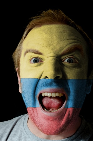 columbian: Low key portrait of an angry man whose face is painted in colors of columbian flag