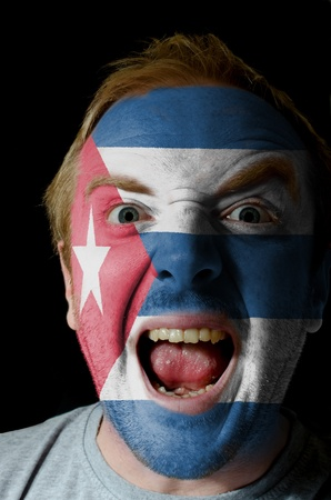 whose: Low key portrait of an angry man whose face is painted in colors of cuban flag