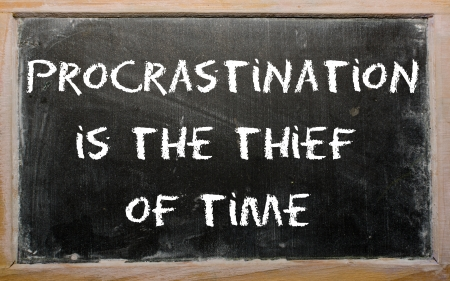 Blackboard writings Procrastination is the thief of time photo