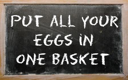 """Los escritos de pizarra """"poner todos los huevos en una canasta"""" Foto de archivo"""