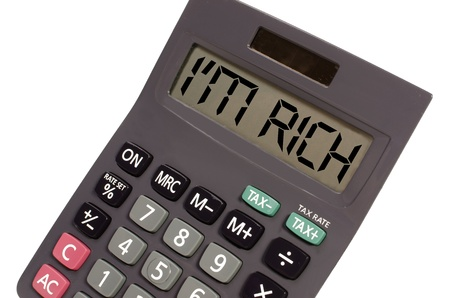I'm rich written on display of an old calculator on white background in perspective photo