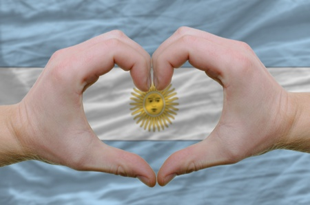 Gesture made by hands showing symbol of heart and love over argentinian flag