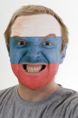 whose: High key portrait of an angry man whose face is painted in colors of russia flag
