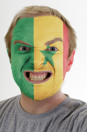 High key portrait of an angry man whose face is painted in colors of senegal flag photo