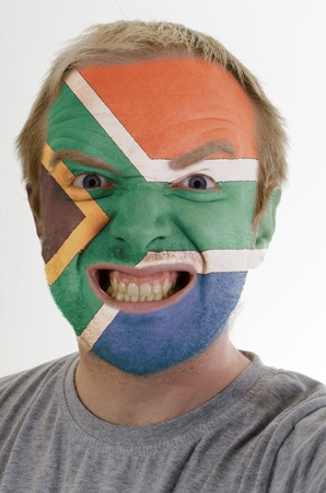 High key portrait of an angry man whose face is painted in colors of south african republic flag photo