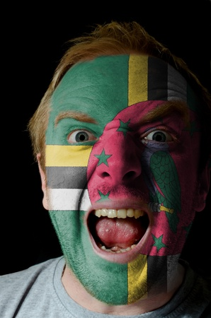 whose: Low key portrait of an angry man whose face is painted in colors of dominica flag